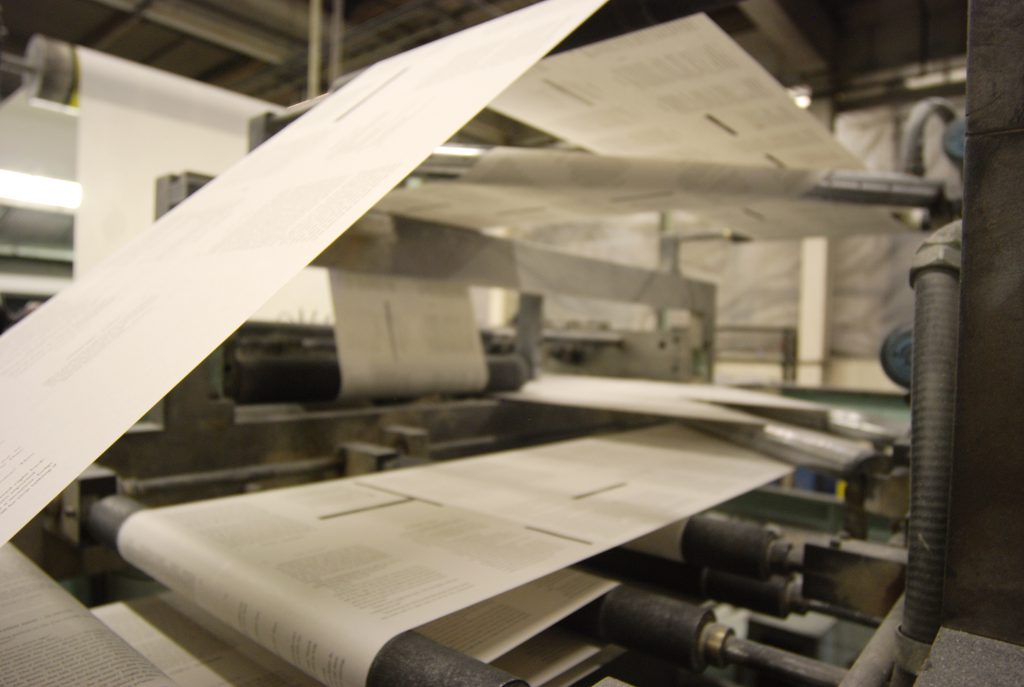 Printed web paper running through crossover rollers
