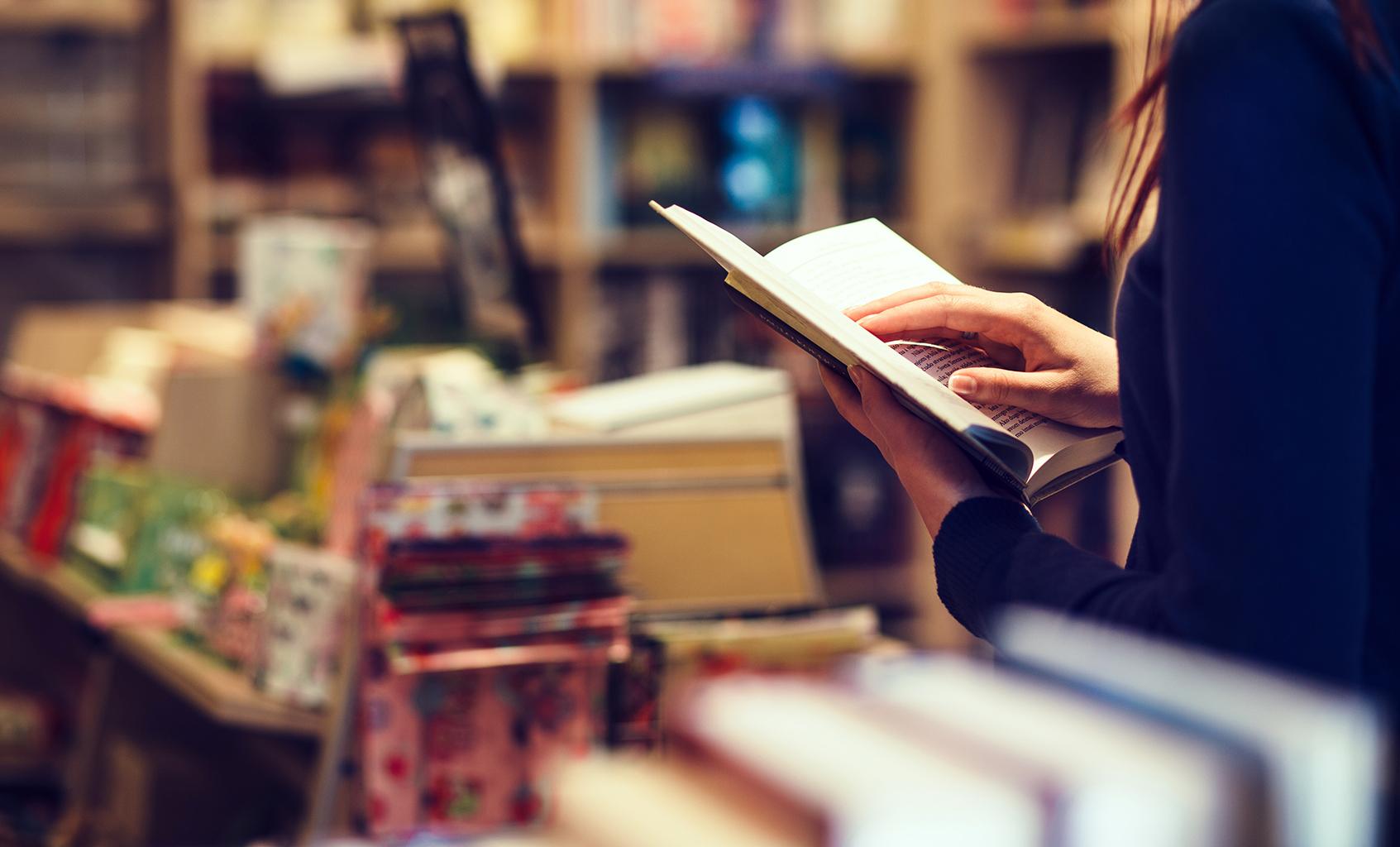Lady holding an open book inside bookshop