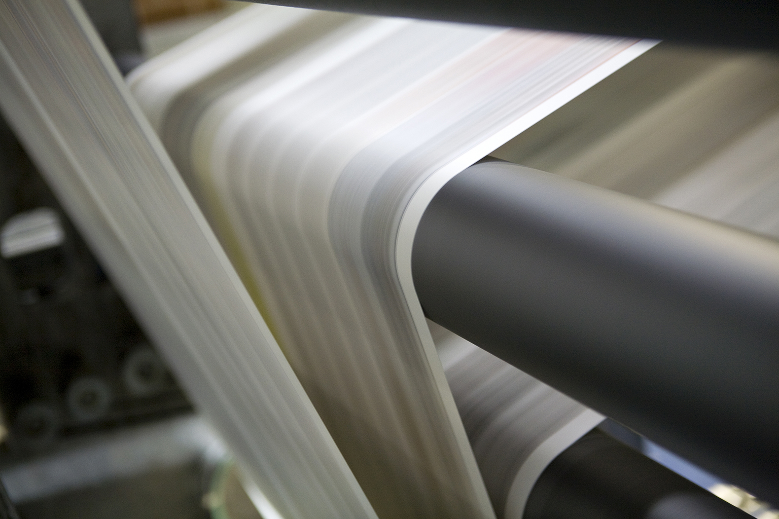 Paper travelling through print machine rollers at speed.